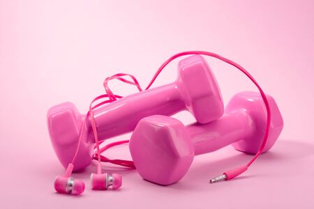 Pink dumbbells and in-ear headphones. Sport and fitness Stock fotó