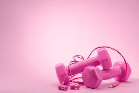 Dumbbells and in-ear headphones on pink background Stock fotó