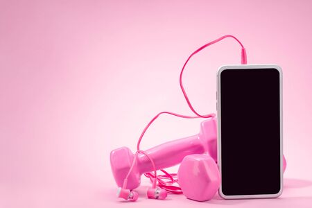 Phone, headphones and dumbbells on pink background Stock fotó - 142326057