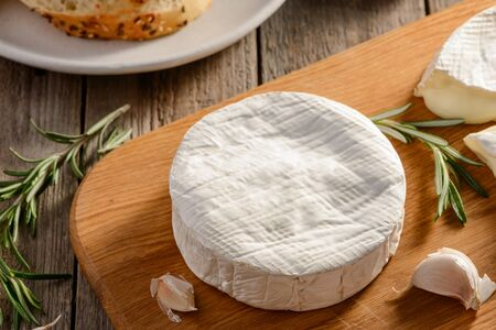 Closeup on a whole wheel of Brie cheese, garlic and rosemary