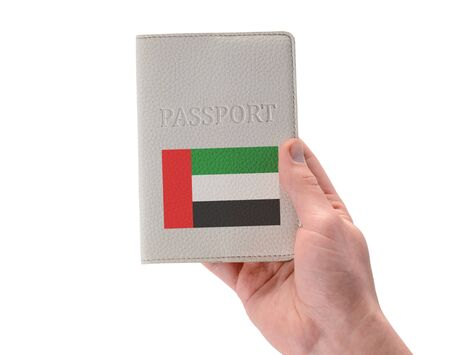 UAE passport in a mans hand on white background