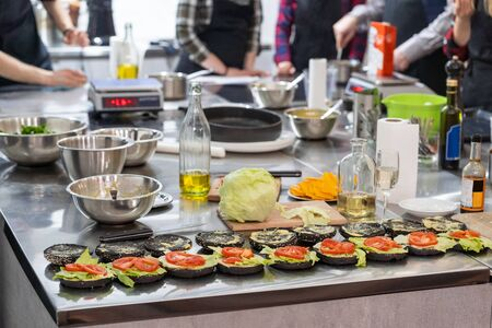 Putting ingredients of burger together at a culinary school