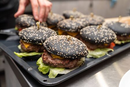 Chef cooking a batch of black burgers