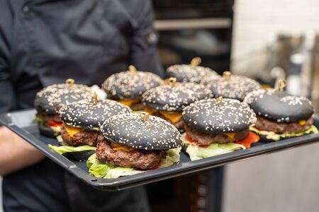 Chef showing a tray full of classic burgers with black buns