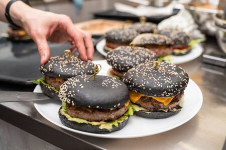 Man putting finished black burgers onto a plate