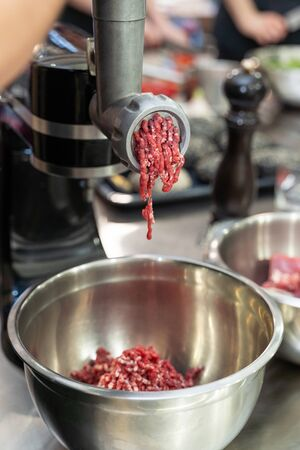 Minced raw meat coming out of an electric grinder. Making ground beef with modern kitchen equipment.