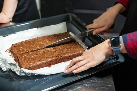 Woman cutting freshly baked brownie cake in two. Bakery classes at a culinary school.