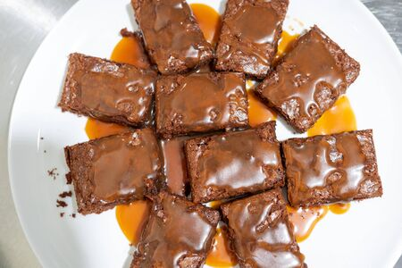 Top view on a plate with brownie pieces poured with salted caramel sauce. Dessert that makes life sweeter and happier with every bite.