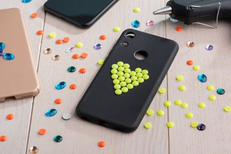 Black plastic case decorated with yellow bead heart