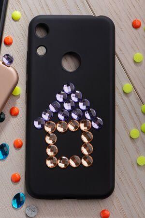 Black phone case with a rhinestone house art Stock Photo