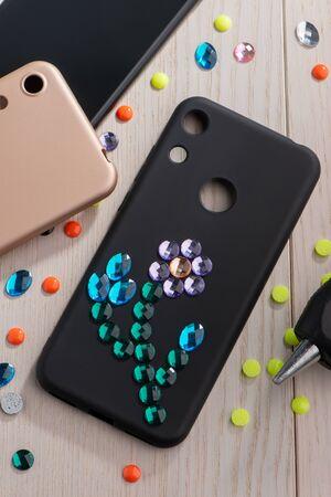 Black phone case with rhinestone flower art