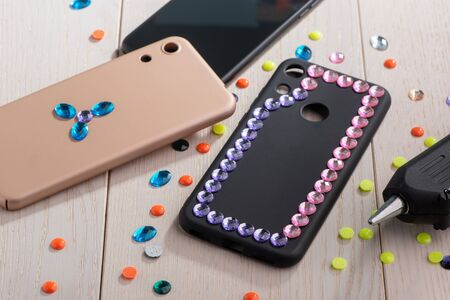 Phone cases being decorated with various rhinestones Banco de Imagens