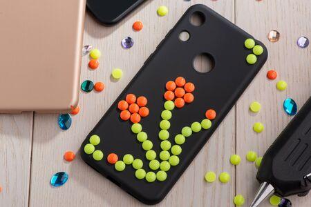 Black phone case adorned with flower bead art