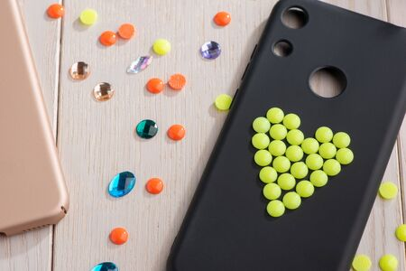 Black mobile phone case decorated with yellow bead heart Banco de Imagens