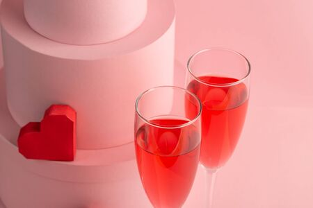 Close-up on two glasses of red sparkling wine and heart on pink background