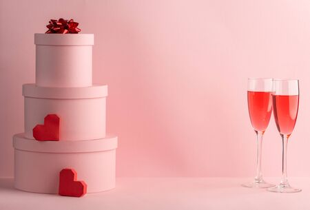Stack of round gift boxes, red hearts and glasses of red wine for two