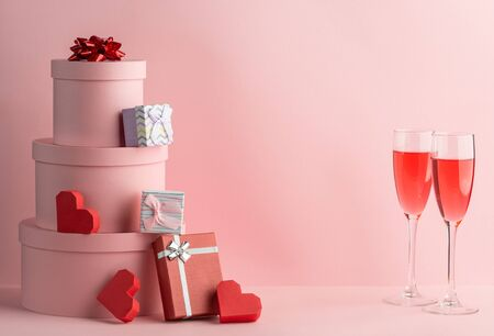 Pile of gift boxes, red hearts and glasses of prosecco on pink background Stockfoto