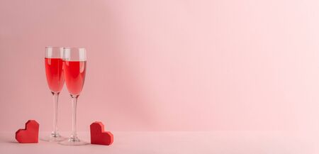 Two glasses of prosecco and red hearts on pink background Stockfoto