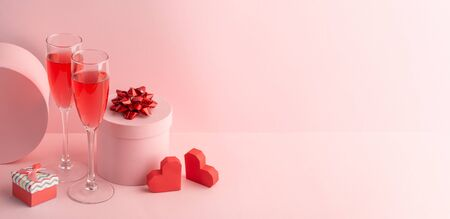 Round gift boxes, red hearts and glasses of sparkling wine on pink background Stockfoto