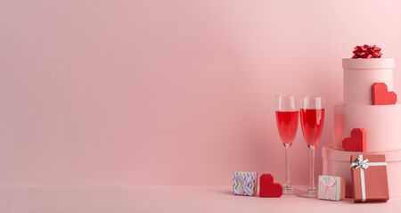 Glasses of red sparkling wine, gift boxes and red hearts on pink background