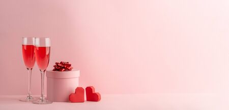 Glasses of red prosecco, round gift box and red hearts on pink background