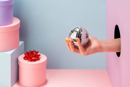 Womans hand holding a mini disco ball on blue and pink background