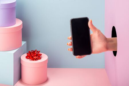 Womans hand holding a cell phone on blue and pink background