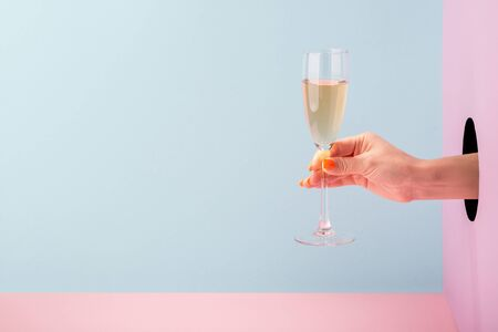 Womans hand holding a glass of champagne