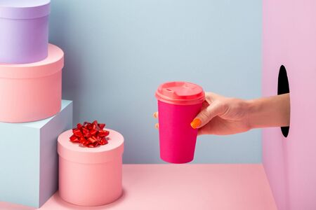 Womans hand holding a pink paper cup of coffee on blue and pink background Standard-Bild
