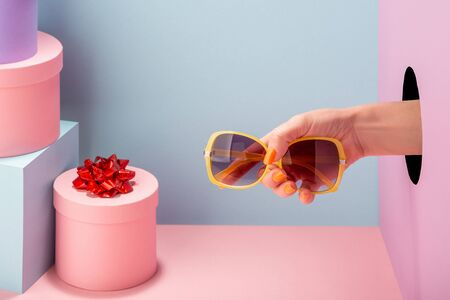 Hand holding a yellow sunglasses on blue and pink background Standard-Bild