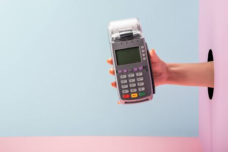 Hand holding a POS terminal with printed receipt on blue and pink background