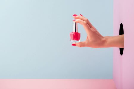 Womans hand holding a bottle of pink nail polish Standard-Bild