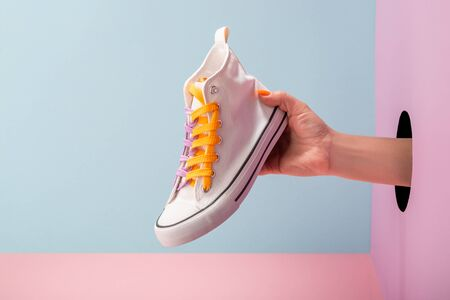 Womans hand holding a white sneaker on blue and pink background