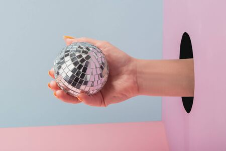 Close-up on womans hand holding a disco ball on blue and pink background