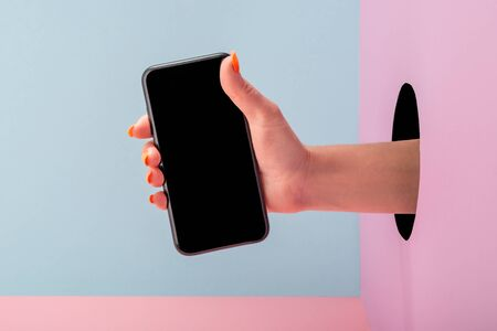 Close-up on womans hand holding a phone on blue and pink background