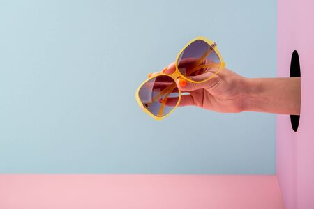 Womans hand holding yellow eyeglasses on blue and pink background