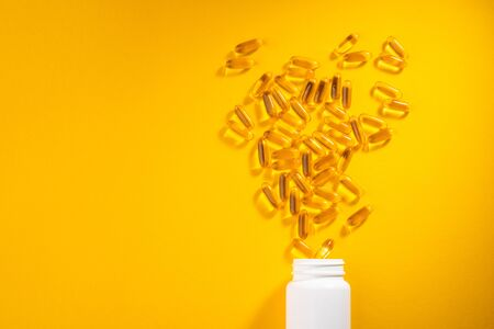 Yellow capsules scattered from a bottle on orange background