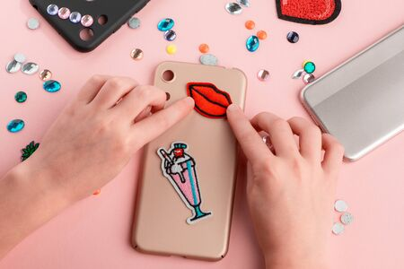 Girl attaching embroidered patches onto beige phone case