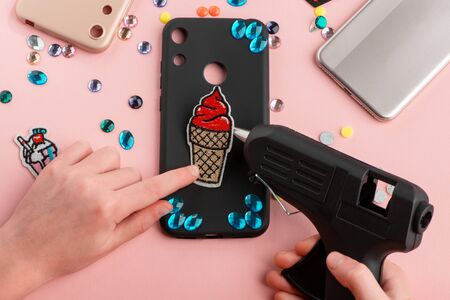 Girl attaching red ice cream patch onto black phone case with a glue gun Stock Photo