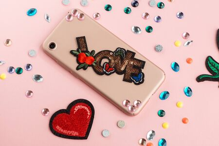 Girl attaching rhinestones and embroidered patch onto beige phone case