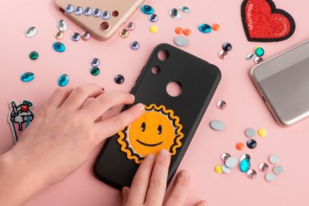 Girl putting a sun smile patch onto black phone case Imagens