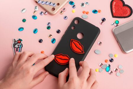 Girl putting red lips patches on black phone case Imagens