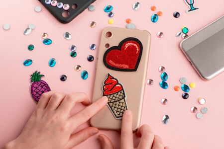Girl putting red heart and ice cream patches onto beige phone case Imagens
