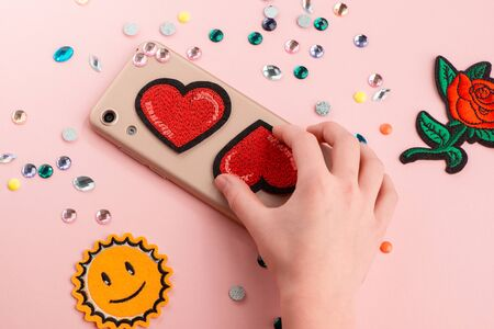 Girl putting red hearts on beige phone case