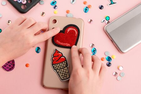 Girl putting red heart and ice cream patches onto beige phone case Фото со стока - 148444043