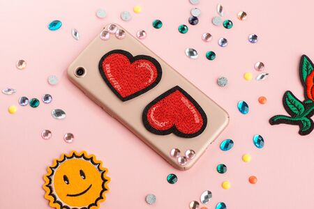 Rhinestones and red heart patch on beige phone case. Various craft materials on pink background. Imagens