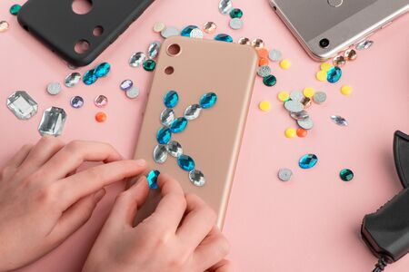 Girl putting blue rhinestone K letter onto beige phone case