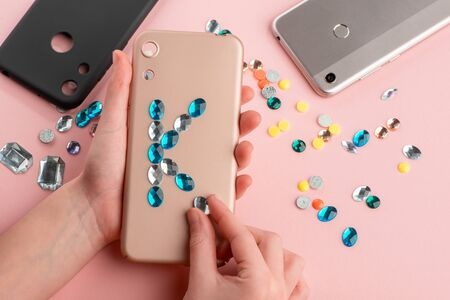 Girl putting blue rhinestone letter onto beige phone case