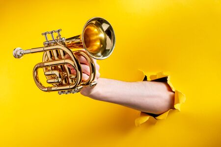 Hand giving a pocket trumpet through a torn hole