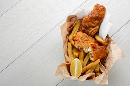 Batter cod and French fries with lemon in paper wrapper